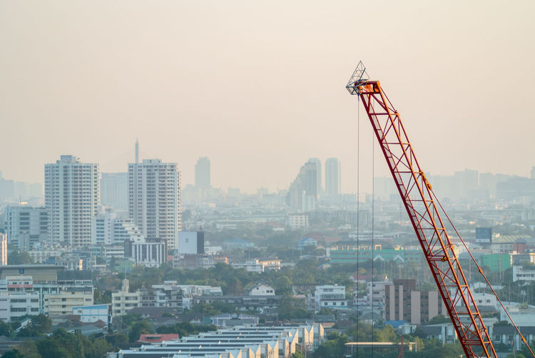 Crane in city against clear sky