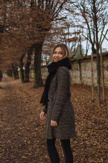 Smiling woman walking against trees at park