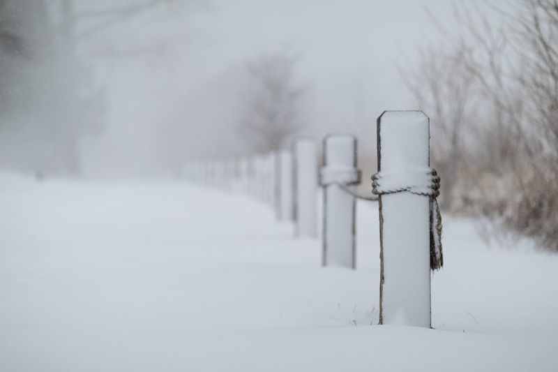 Snow covered wooden post on field during winter