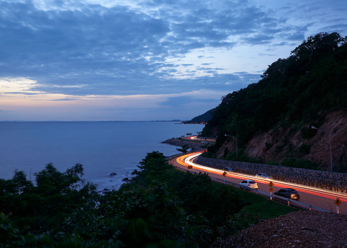 Chanthaburi, Thailand-July 14, 2019: Beautiful road along coastline and light form car after sunset. View from viewpoint of the queen nang hill View Landscape Point Scenic Holiday Thailand Phaya Sea Nature Road Blue Chanthaburi Background Sky Water Travel Outdoor Queen Nang Ocean Curve Beach Mountain Landmark Summer Viewpoint Beautiful Sunset Seaside Coastline Beauty Hill Natural Vacation Wave Tropical Tourism LINE Relax Yellow Long Exposure Blue Hour View, Landscape, Point, Scenic, Holiday, Thailand, Phaya, Sea, Nature, Road, Blue, Chanthaburi, Background, Sky, Water, Travel, Outdoor, Queen, Nang, Ocean, Curve, Beach, Mountain, Landmark, Summer, Viewpoint, Beautiful, Sunset, Seaside, Seascape, Coastline, Beauty, Hill, Natural, Vacation, Wave, Tropical, Concept, Tourism, Line, Relax, Yellow, Long Exposure, Blue Hour Scenics - Nature Cloud - Sky Beauty In Nature Tranquil Scene Idyllic Outdoors Non-urban Scene