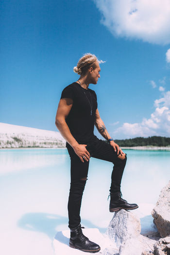 Curly blond man dressed in all black. posing on the sea beach. Impressive shoot, trendy hairstyle. Summer time. Adult Beauty In Nature Casual Clothing Day Full Length Leisure Activity Lifestyles Looking Nature One Person Outdoors Real People Scenics - Nature Sky Standing Water Young Adult Young Women