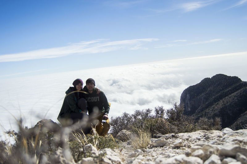 Couple sitting on rock against cloudscape