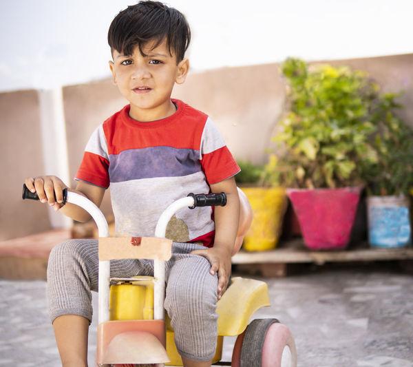 Portrait of boy sitting in toy car
