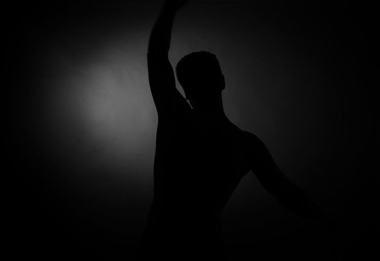 Silhouette of man against black background
