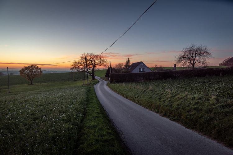 Sky Plant Sunset Road Tree Field The Way Forward Grass Landscape Tranquility Direction No People Tranquil Scene Transportation Nature Land Scenics - Nature Beauty In Nature Environment Non-urban Scene Outdoors Diminishing Perspective Electricity