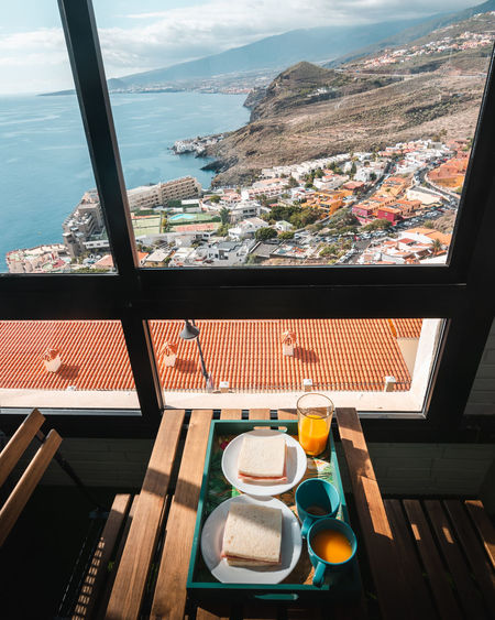 Breakfast of orange juice and sandwich from a terrace with views of the mountains and the coast