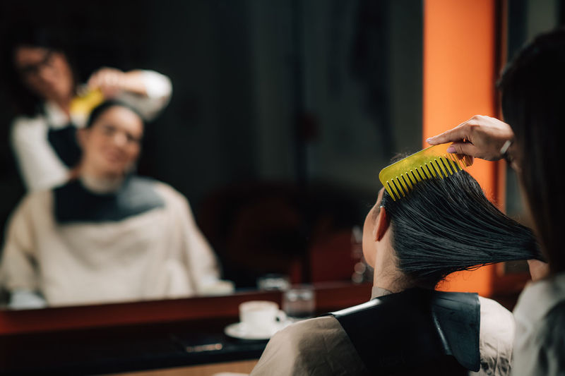 Hairdresser combing customer hair in salon