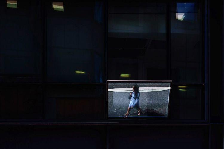 Woman seen through glass window at night