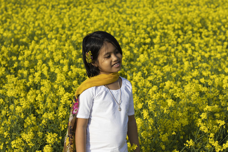 A beautiful indian girl child in white dress standing near yellow mustard flower field