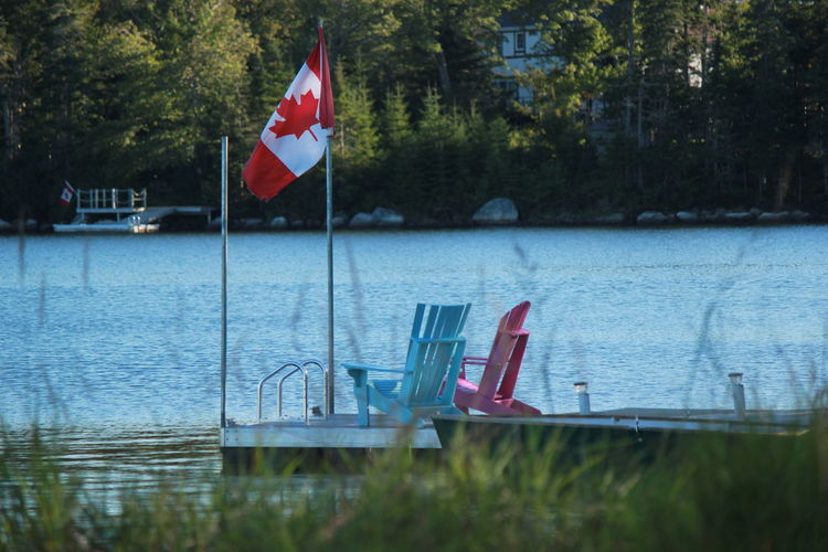 Blue Canadian Canadian Flag Day Depth Of Field Flag Focus On Background Lake National Flag Outdoors Patriotism Pole Recreational Pursuit Relaxation Selective Focus Vacation Water