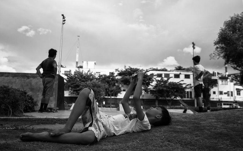 People relaxing in city against sky