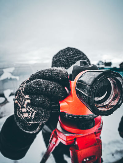 Close-up of person photographing at snow field