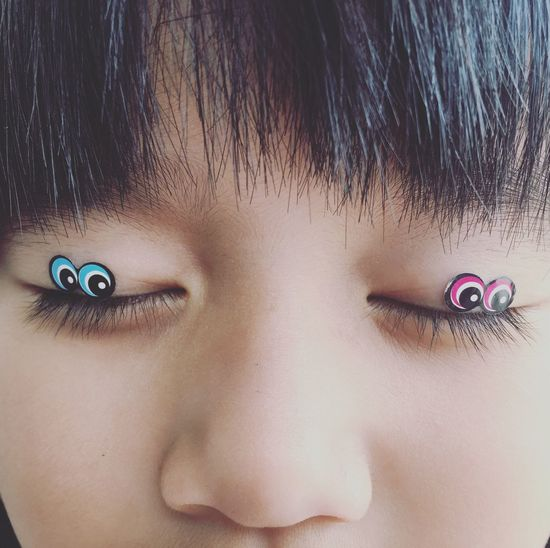 Close-up of cute girl with googly eyes