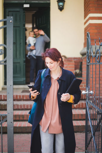 Full length of young woman using phone while standing against built structure