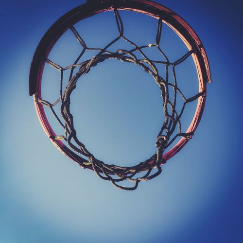 Directly below shot of basketball hoop against clear blue sky