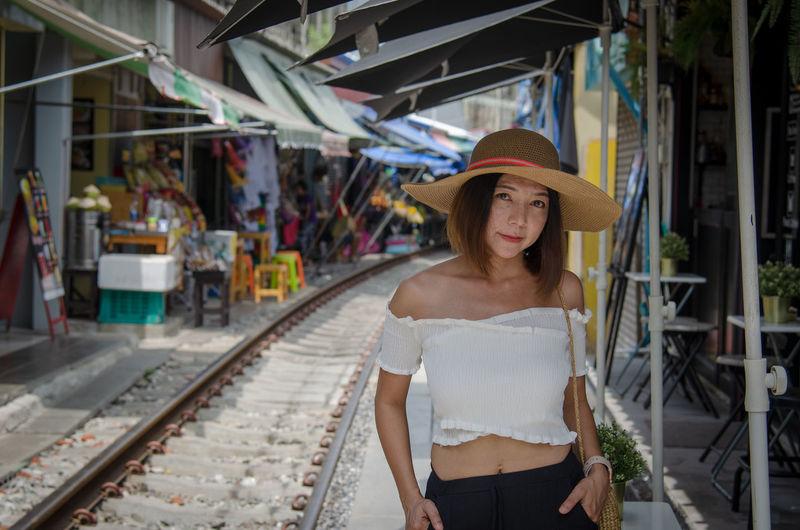 Portrait of woman standing at railroad station platform