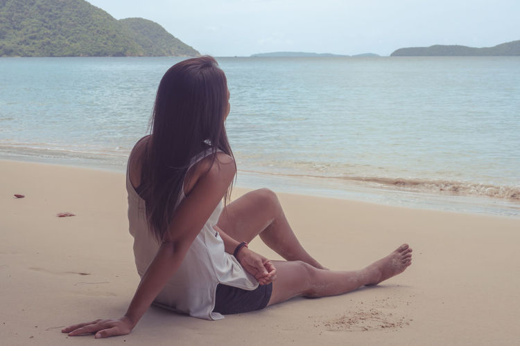 Woman sitting on shore at beach