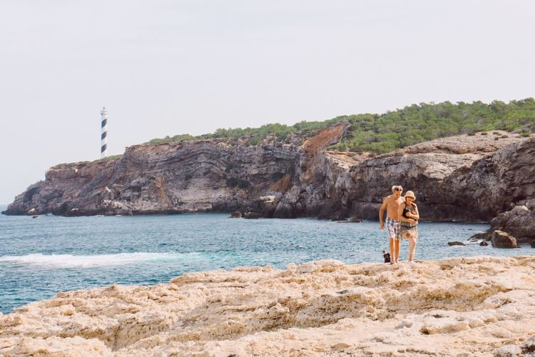 EyeEm Selects Rock - Object Sea Nature Two People Clear Sky Beach Day Cliff Outdoors Togetherness Men Beauty In Nature Standing Full Length Water Sky People Adult Ibiza Portinatx Beauty In Nature Lifestyles Leisure Activity Real People