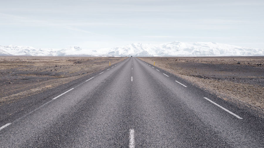 Empty road passing through landscape against sky