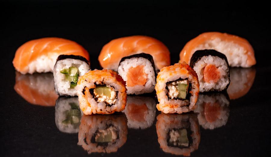 Close-up of sushi against black background