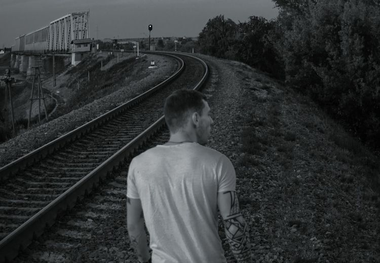 Rear view of man standing by railroad tracks