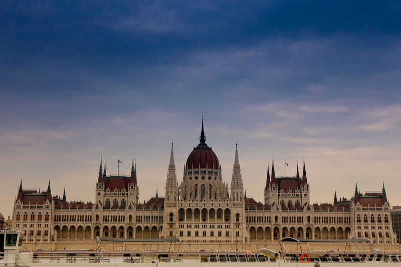 Hungarian parliament building in city against sky during sunset