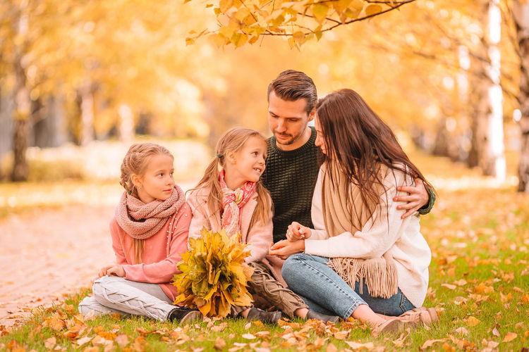 Full length of father and girl sitting on autumn leaves