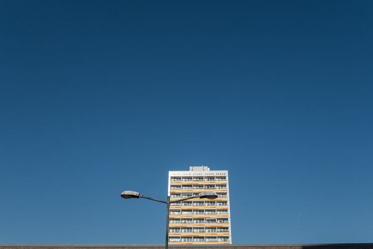 Low Angle View Of Street Light And Residential Building Against Clear Blue Sky