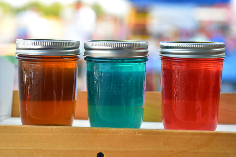 Row of glass jars of colorful artisanal jelly in glass jars at farmer's market