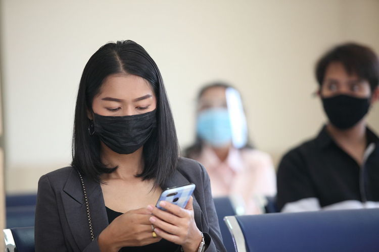 Woman wearing face mask using mobile phone in waiting room
