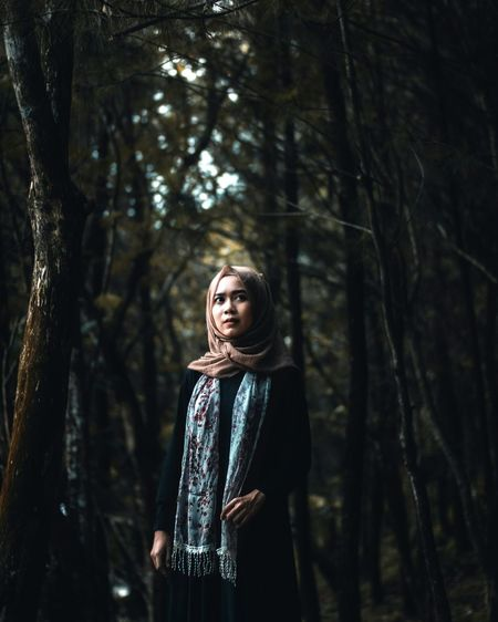 Young woman wearing hijab in forest