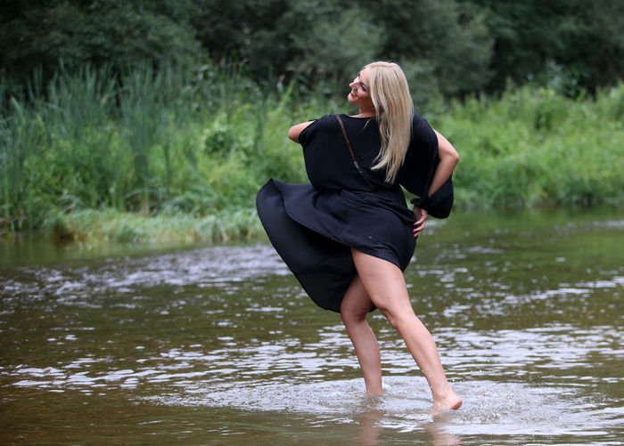 Full length of young woman standing in lake