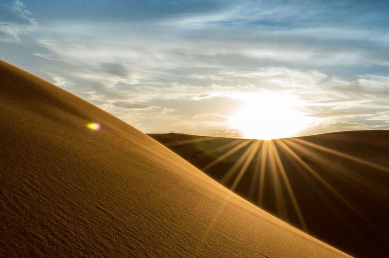 Scenic view of sandy desert against sky on sunny day