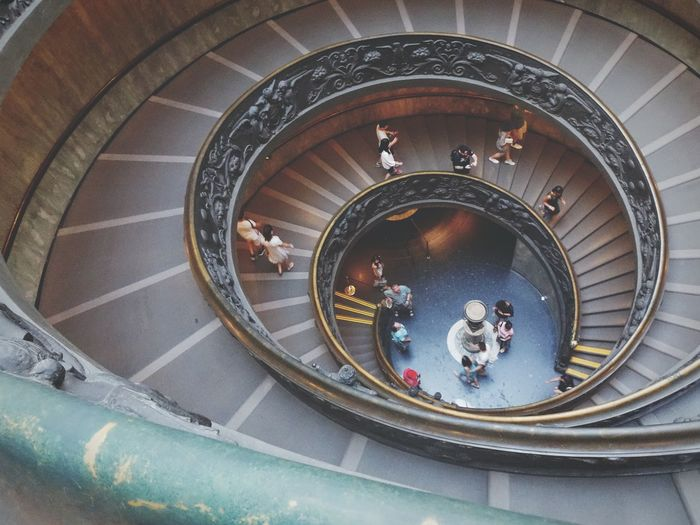High Angle View Of People Moving Down Spiral Staircase At Museum