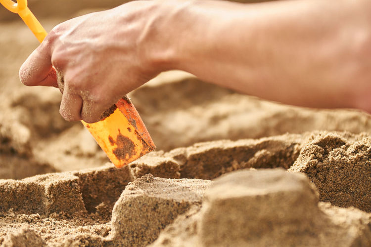 Cropped image of person holding shovel on sand at beach