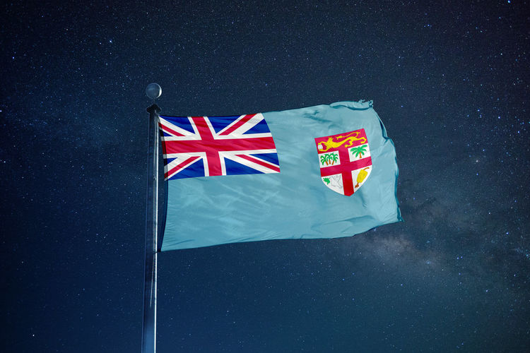 Low Angle View Of Fijian Flag Against Star Field Sky