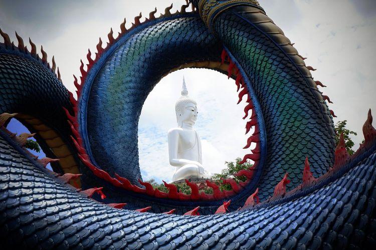 Buddha statue seen through dragon sculpture