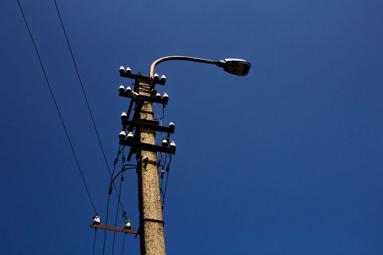 Low angle view of street light against clear blue sky during sunny day