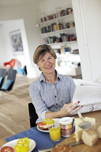 Smiling woman holding smart phone at home