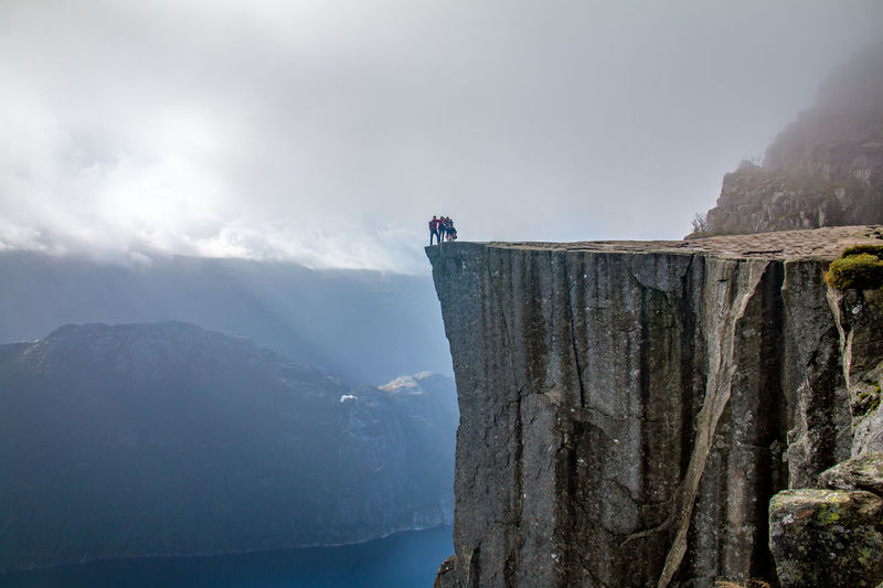 Adventure Beauty In Nature Challenge Cliff Cloud - Sky Day Fog Full Length Hiking Landscape Leisure Activity Low Angle View Mountain Mountain Peak Mountain Range Nature Outdoors Preikestolen Real People RISK Rock - Object Scenics Sky Tranquil Scene Tranquility