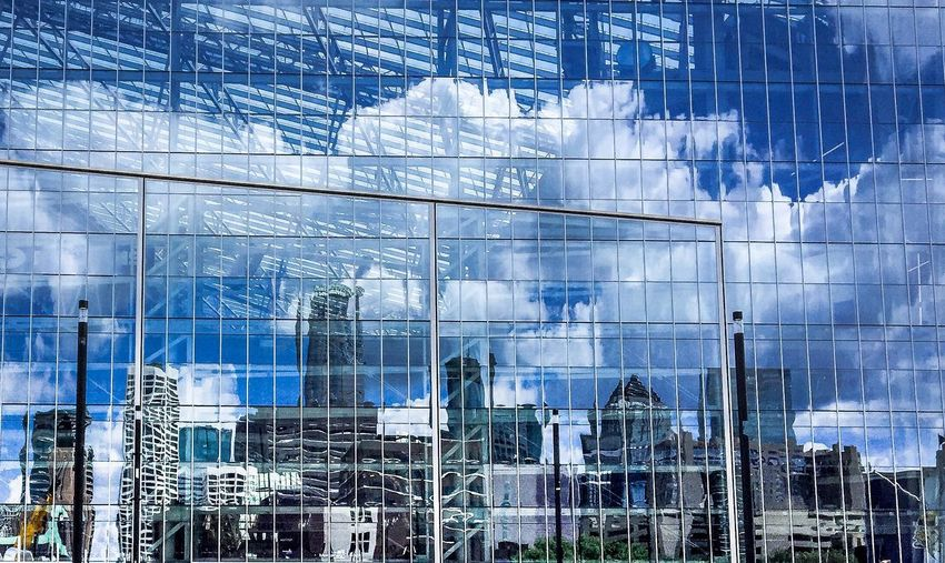 Clouds over buildings reflecting on glass windows
