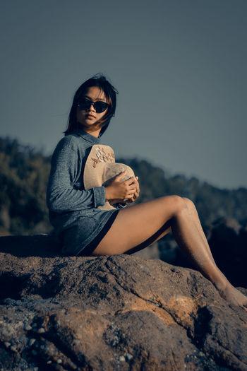 Woman sitting on rock on the beach