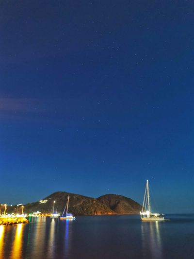 Sailboats in sea against clear sky at night