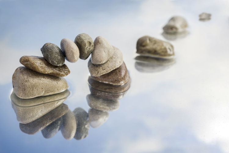 arch, bridge or gate made of balanced pebbles with reflection in the water, blue sky with clouds, copy space Cohesion Gate Meditation Teamwork Arch Balance Blue Bridge Clouds Concept Equality Focus On Foreground Harmony Health Mental Health  Pebbles Poise  Reflection Sky Solid Still Life Stone Symbol Water Zen