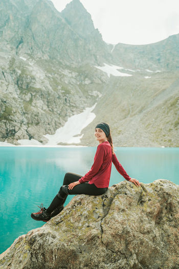 Woman sitting on rock by mountains