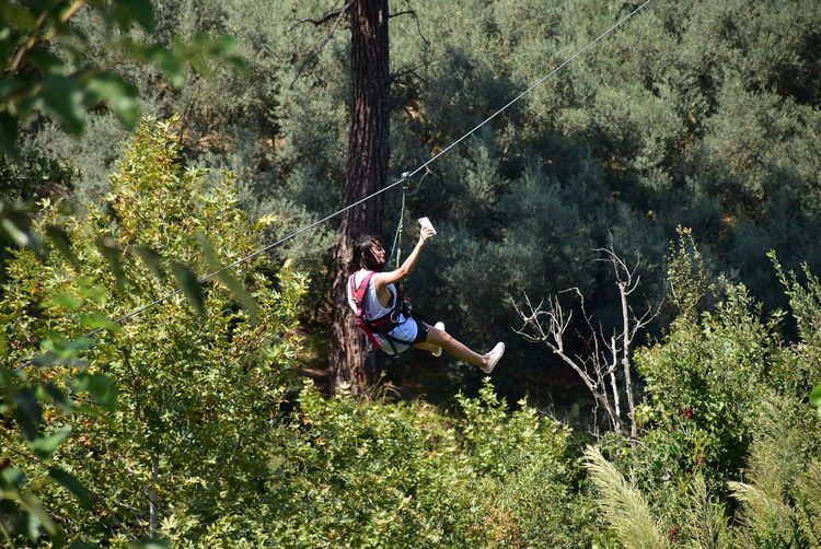Woman hanging on rope in forest