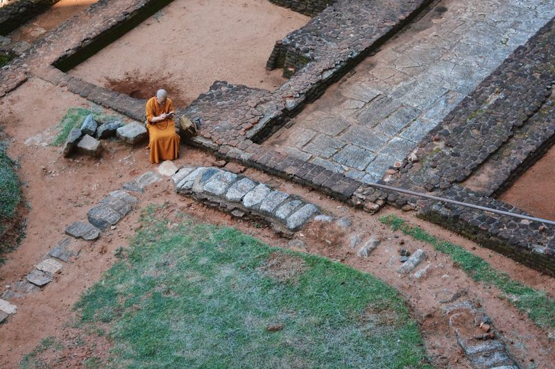 Buddhist monk reading 📖 Bhikkhu Asian  ASIA Traveling Travel Sri Lanka Reading Monk  Bhikkhu Buddha Buddhism Green Color Orange Color High Angle View Day Outdoors Architecture Built Structure Real People Building Exterior Nature One Person People Statue