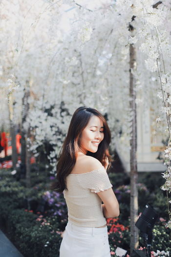 My Best Photo International Women's Day 2019 Streetwise Photography One Person Young Adult Long Hair Hair Standing Hairstyle Young Women Smiling Real People Beautiful Woman Casual Clothing Plant Women Lifestyles Leisure Activity Focus On Foreground Tree Beauty Looking At Camera Outdoors
