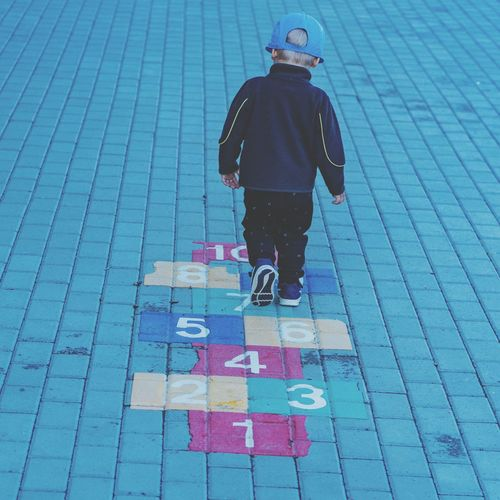 Rear view of boy playing hopscotch on footpath