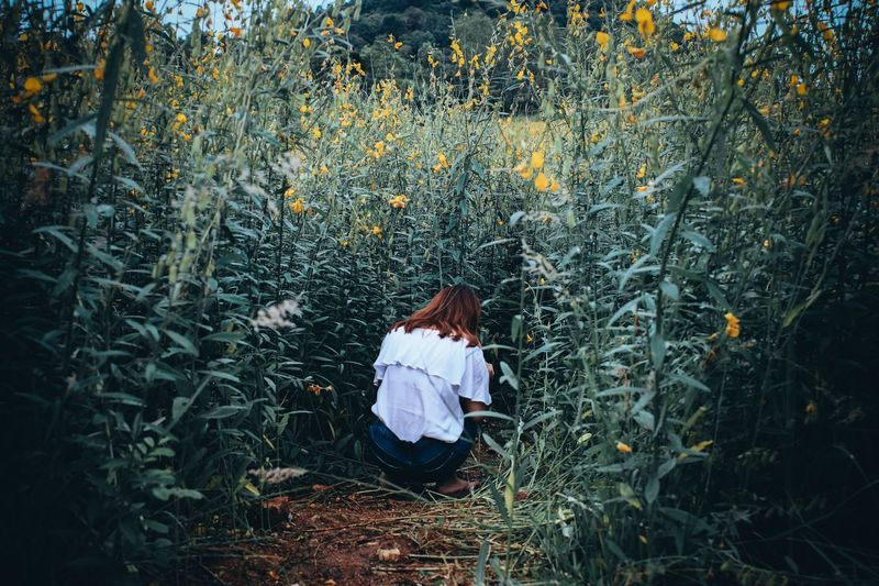 Rear View Of Woman Crouching On Field Amidst Plants